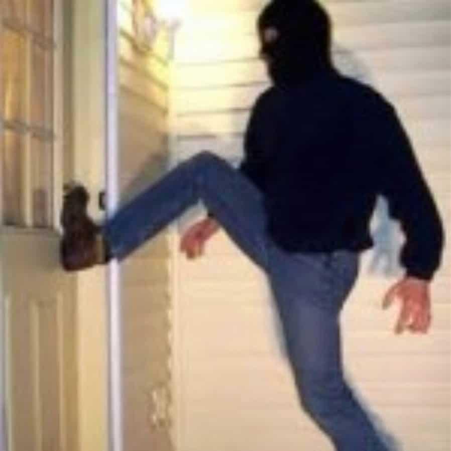 Burglar kicking in door